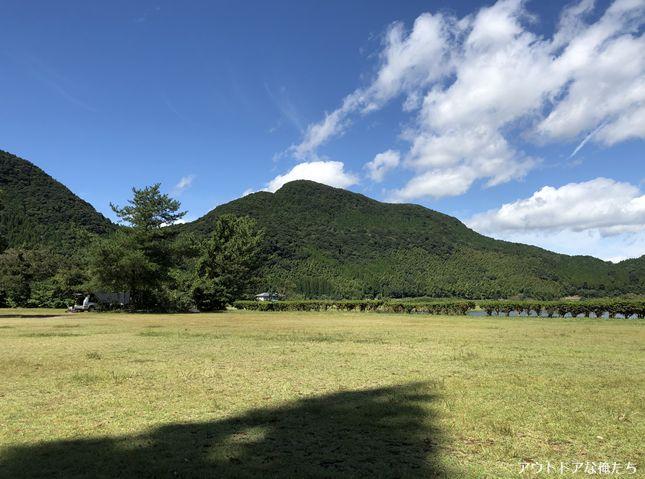 芝生キャンプ場と山と雲